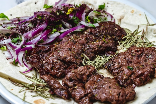 Vista lateral kebab carne de ternera a la plancha con cebolla roja y romero sobre pita