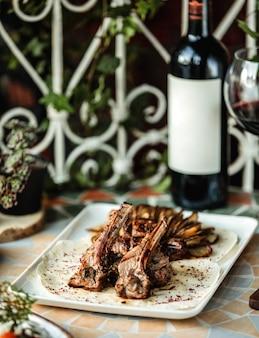 Vista lateral de kebab de costilla de cordero con papas al horno sobre la mesa con una botella de vino tinto