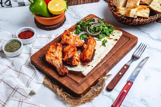 Vista lateral kebab de pollo en pan de pita con hierbas y cebollas en una pizarra