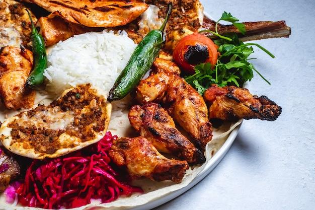 Vista lateral kebab de pollo con pimiento verde caliente a la parrilla tomate encurtido y arroz sobre pita