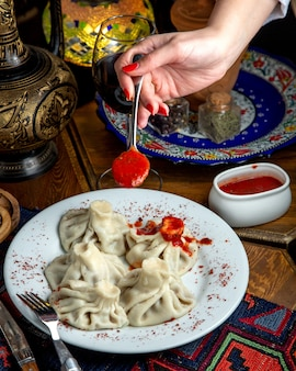 Vista lateral del khinkali georgiano tradicional y una mano de mujer sosteniendo una cuchara con salsa de tomate picante