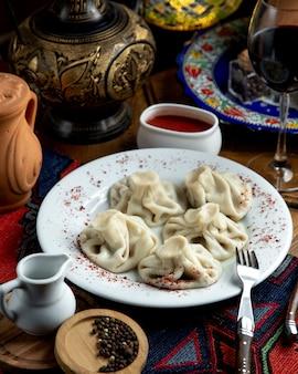 Vista lateral del khinkali georgiano tradicional con sumakh y salsa picante en un plato blanco