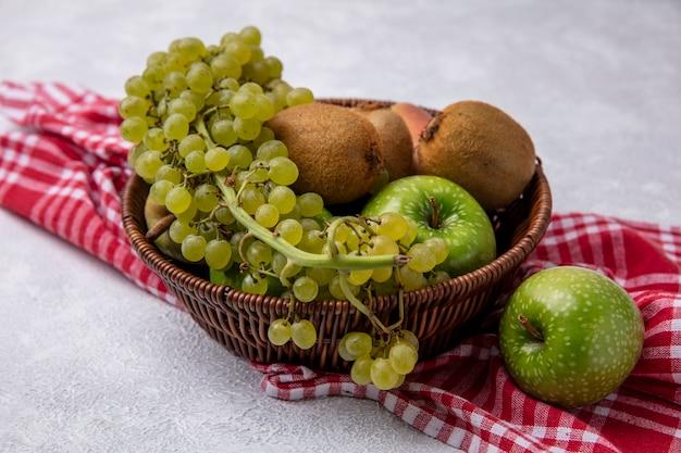 Vista lateral de kiwi con manzanas verdes, uvas y peras en una canasta sobre una toalla a cuadros rojos sobre un fondo blanco.