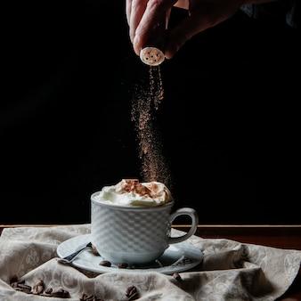Vista lateral latte con granos de café y canela y mano humana en taza blanca