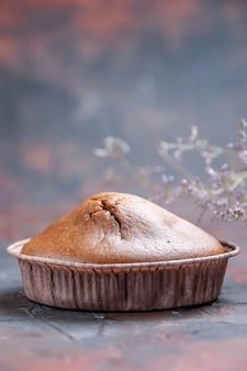Vista lateral desde lejos cupcake un apetitoso cupcake de chocolate junto a las ramas de los árboles