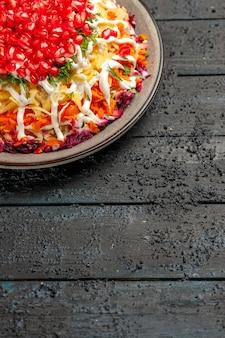 Vista lateral desde lejos plato de navidad ensalada de navidad con patatas zanahorias mayonesa y semillas de granada en la mesa de madera