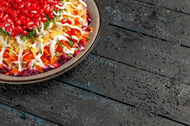Vista lateral desde lejos plato de navidad ensalada de navidad con patatas zanahorias remolacha mayonesa y granada en la mesa gris