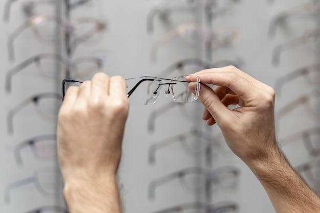 Vista lateral de lentes transparentes sostenidos por el hombre