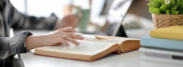 Vista lateral del libro de lectura de estudiantes universitarios para prepararse para su próximo examen