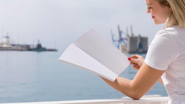 Vista lateral del libro de lectura de la mujer junto al lago con espacio de copia
