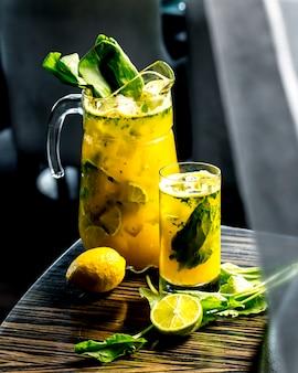 Vista lateral de limonada vigorizante con lima limón y espinacas