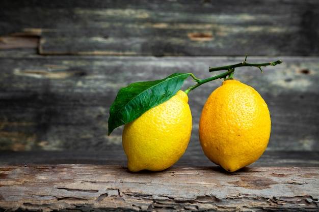 Vista lateral de limones con y sin hojas sobre fondo de madera oscura. horizontal