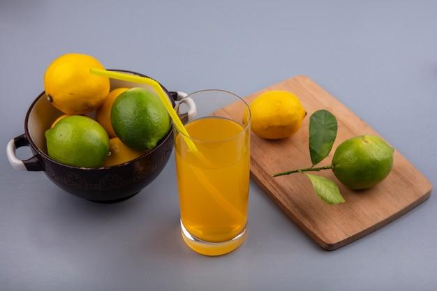 Vista lateral de limones con limas en una cacerola con tabla de cortar y jugo de naranja sobre fondo gris