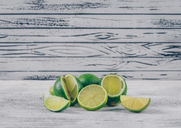 Vista lateral de limones verdes con rodajas sobre fondo de madera gris. horizontal