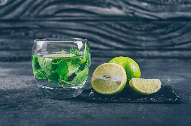 Vista lateral de limones verdes con rodajas en vaso de agua sobre fondo negro con textura. horizontal