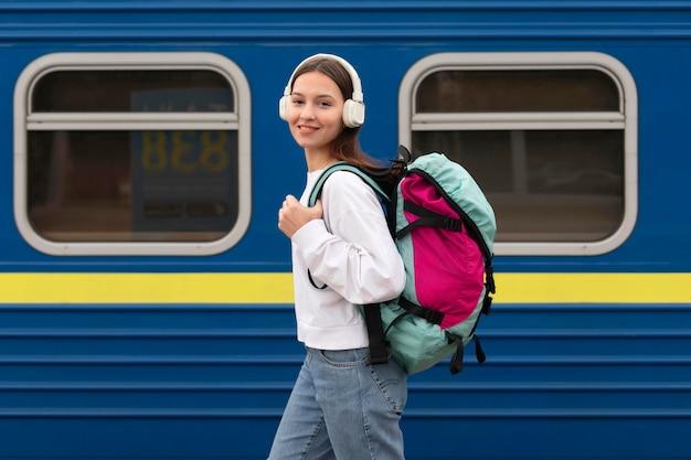 Vista lateral linda chica en la estación de tren escuchando música