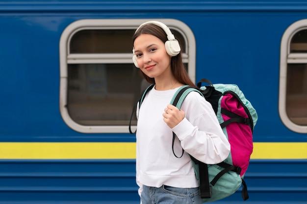 Vista lateral linda chica en la estación de tren sonríe