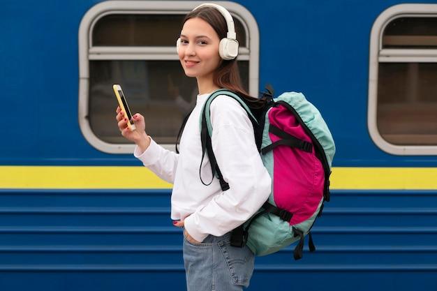 Vista lateral linda chica en la estación de tren con teléfono móvil