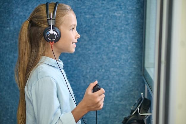 Vista lateral de una linda paciente joven en auriculares audiómetro de pie en la cabina insonorizada