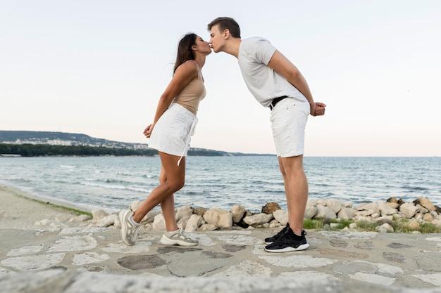 Vista lateral de la linda pareja besándose por el océano