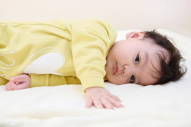 Vista lateral de un lindo bebé asiático con un vestido amarillo, acostado en la cama y mirar a la cámara