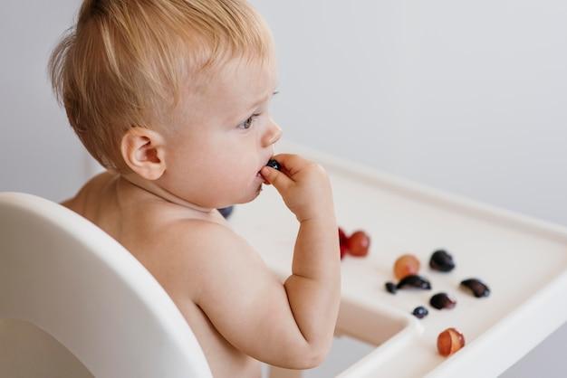 Vista lateral lindo bebé en trona eligiendo qué fruta comer
