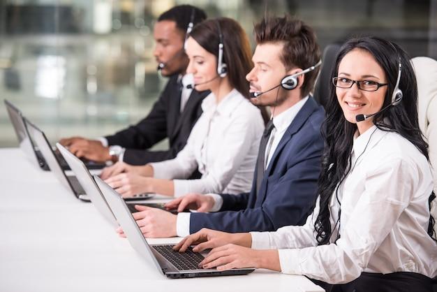 Vista lateral de la línea de los empleados del centro de llamadas están sonriendo.