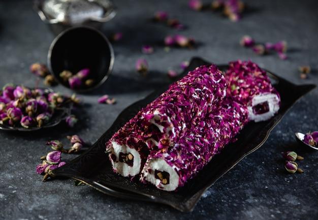 Vista lateral de lokum tradicional delicias turcas con pistachos y flor color de rosa en bandeja antigua en pared negra