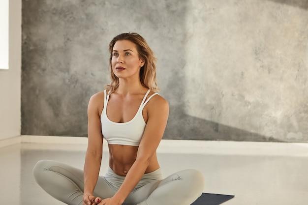 Vista lateral de longitud completa de una hermosa mujer joven en forma en ropa deportiva que se ejercita en el interior, practicando ejercicios de yoga en la colchoneta, haciendo pose de perro boca abajo o pose de saludo al sol de adho mukha svanasana