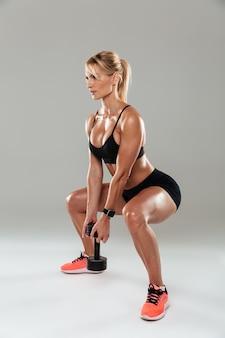 Vista lateral de longitud completa de una mujer joven atleta haciendo sentadillas
