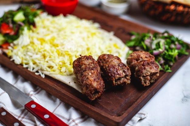Vista lateral de lula kebab con arroz y cebolla