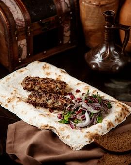 Vista lateral lula kebab con cebolla y hierbas en pan de pita