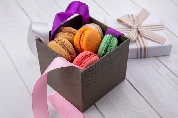 Vista lateral de macarons de colores en una caja con lazos de colores y papel de regalo sobre una superficie blanca