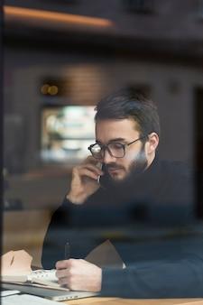 Vista lateral macho joven hablando por teléfono