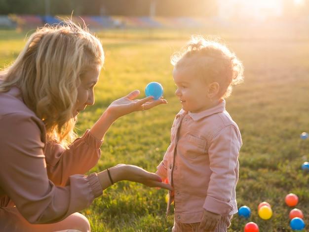 Vista lateral madre e hijo jugando con pelotas de plástico