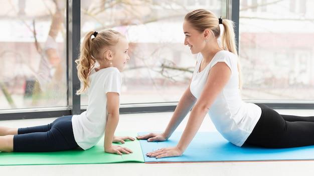 Vista lateral de la madre en la estera de yoga en casa con hija