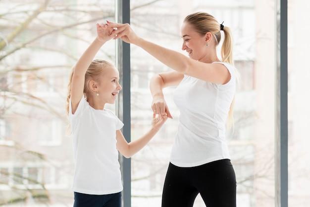Vista lateral de la madre haciendo ejercicio en casa con hija sonriente