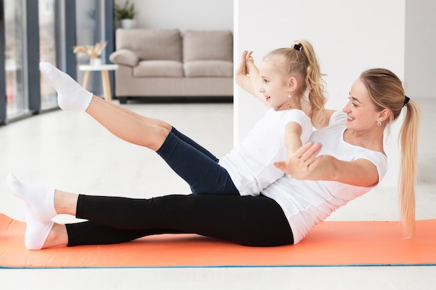 Vista lateral de la madre haciendo ejercicio con su hija en casa en la estera de yoga