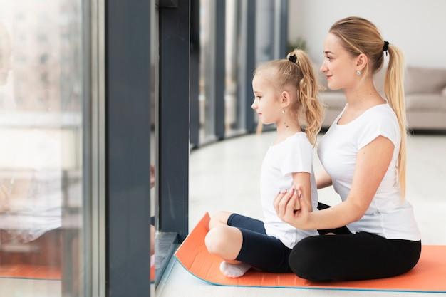 Vista lateral de la madre haciendo yoga con hija en casa