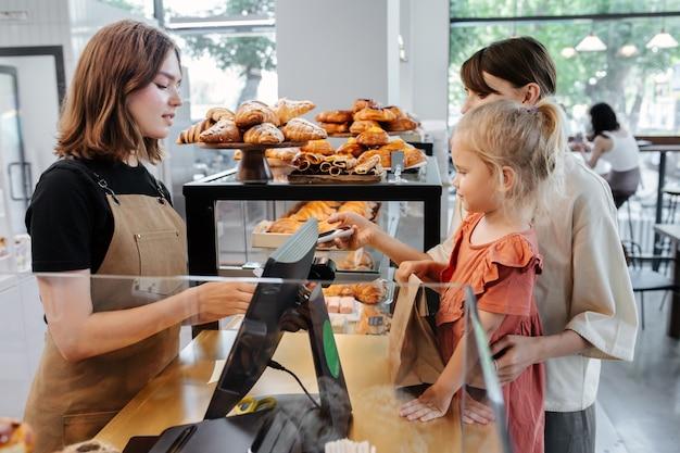 Vista lateral de una madre con una hija comprando pasteles en una panadería. ella paga con su teléfono. la niña está de pie en un escalón y observa las prótesis.