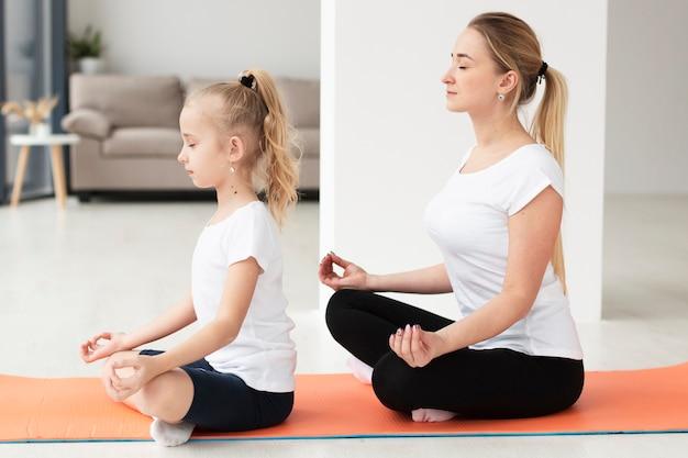 Vista lateral de la madre y la hija haciendo una pose de yoga en casa