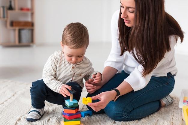 Vista lateral de la madre jugando con el niño en casa