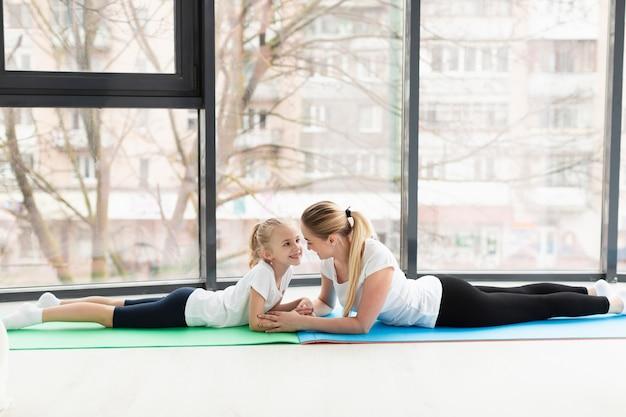 Vista lateral de la madre y el niño en la estera de yoga en casa