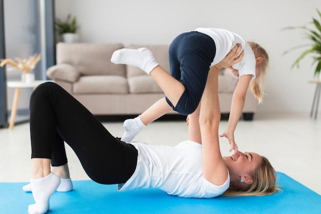 Vista lateral de la madre y el niño haciendo ejercicio en casa