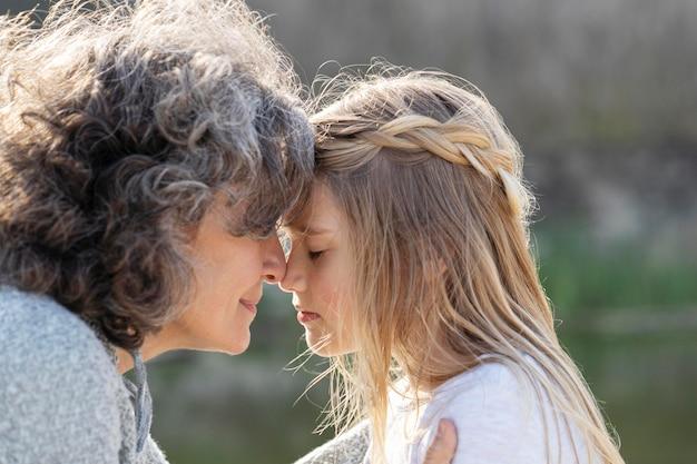 Vista lateral de la madre presionando su frente contra la de su hija