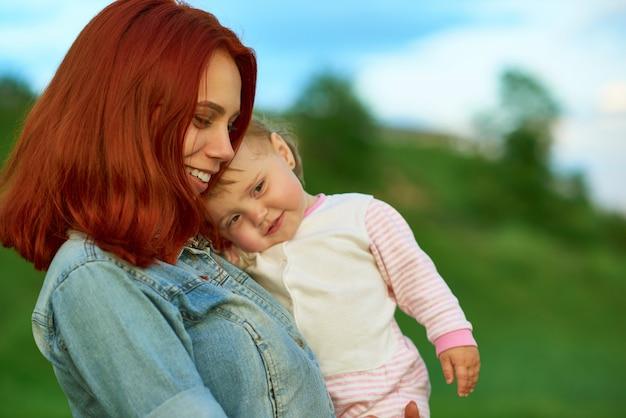 Vista lateral de la madre que guarda al pequeño niño lindo que presenta en campo verde.