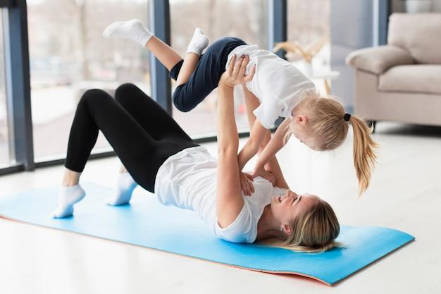 Vista lateral de la madre que levanta a la hija feliz en el aire mientras está en la estera de yoga