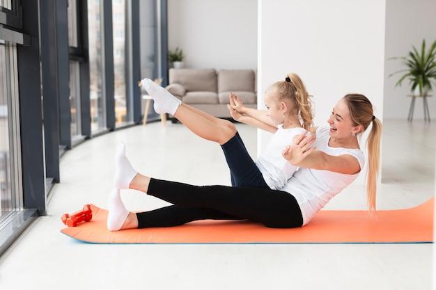 Vista lateral de la madre sonriente haciendo ejercicio con niño en casa