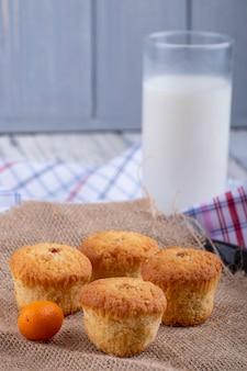 Vista lateral de magdalenas y un vaso de leche sobre la mesa