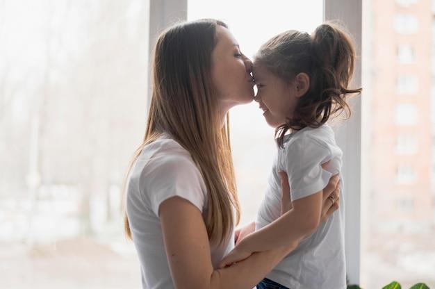 Vista lateral mamá besando a niña en la frente